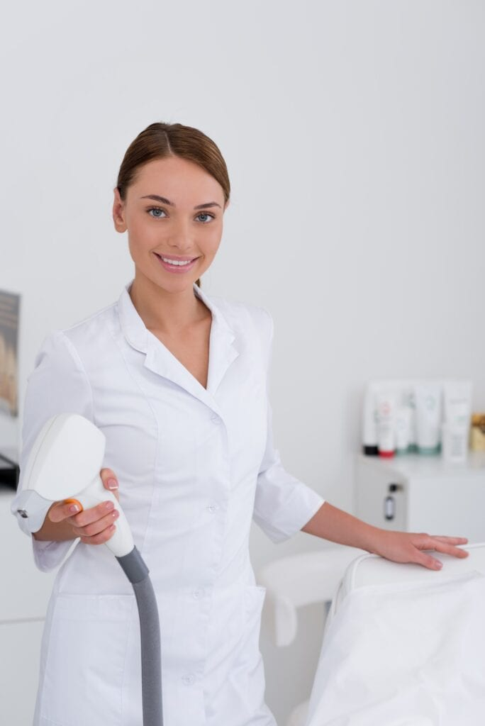 portrait of smiling cosmetologist in white coat with laser apparatus in salon