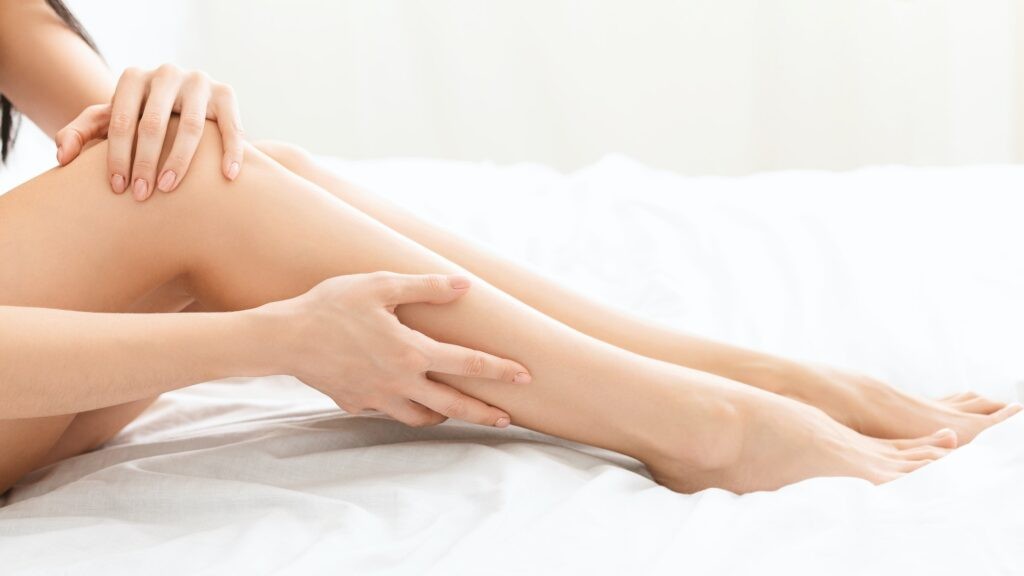 Young woman touching smooth skin of her legs in bed